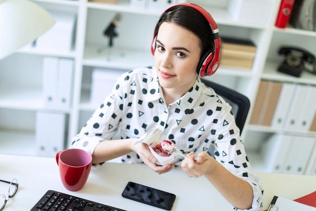 Schönes junges mädchen, das in den kopfhörern am schreibtisch im büro joghurt mit roter füllung essend sitzt.