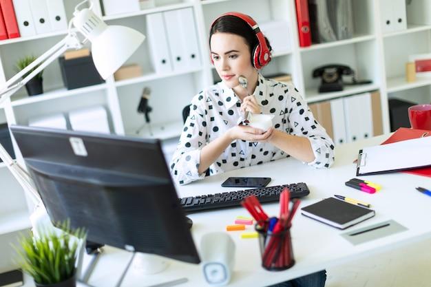 Schönes junges mädchen, das in den kopfhörern am schreibtisch im büro sitzt, joghurt isst und monitor betrachtet.