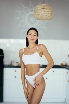Schönes junges mädchen, das in der wäsche in der küche aufwirft. modeporträtmodell in der küche.