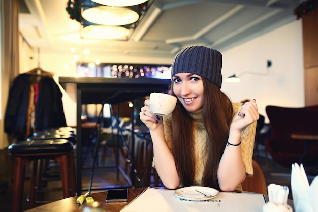 Schönes junges mädchen, das in einem café stillsteht