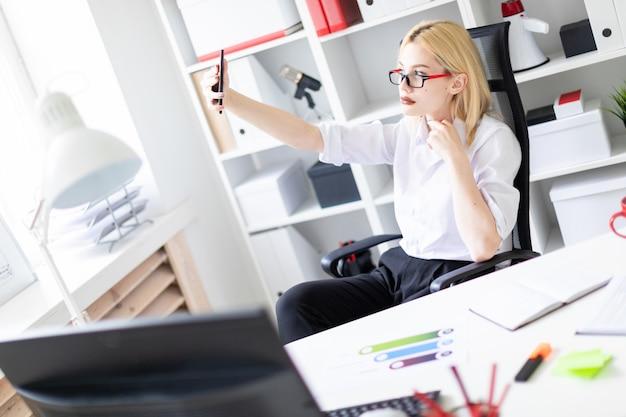 Schönes junges mädchen, das in einem hellen büro an einem computertisch arbeitet. das mädchen hat weiße haare und trägt eine brille. sie trägt ein weißes hemd und eine schwarze hose. foto mit schärfentiefe