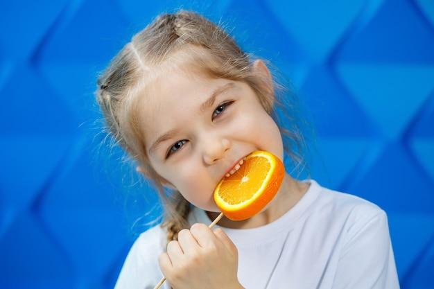 Schönes junges mädchen, das in einem weißen t-shirt gekleidet ist, hält eine halbe orange in ihren händen und lächelt. orangenfrüchte, sie beißt eine orange und sie mag.