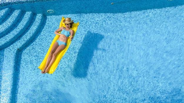 Schönes junges mädchen, das in schwimmbadfrau auf aufblasbarer matratze luftaufnahme entspannt