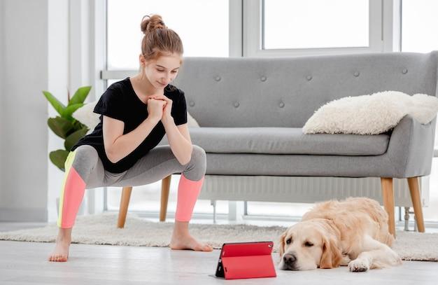 Schönes junges mädchen, das kniebeugen während des online-trainings mit tablette macht. golden retriever hund liegt, während der besitzer trainiert