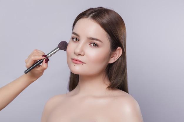 Schönes junges mädchen, das make-up tut
