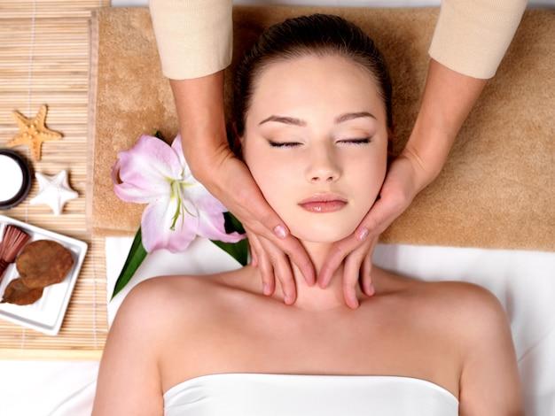 Schönes junges mädchen, das massage für nacken im spa-salon bekommt