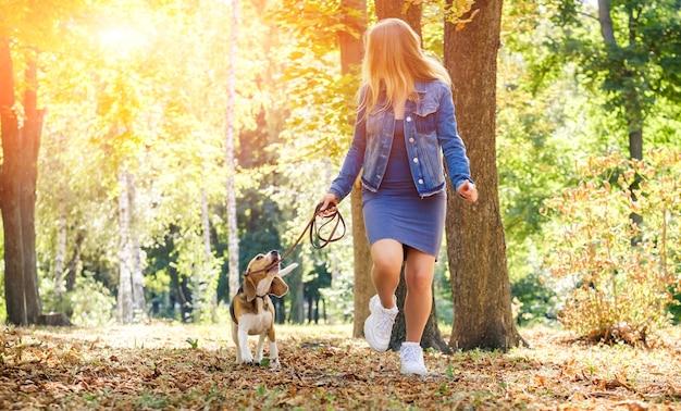 Schönes junges mädchen, das mit beagle-hund im herbstpark läuft
