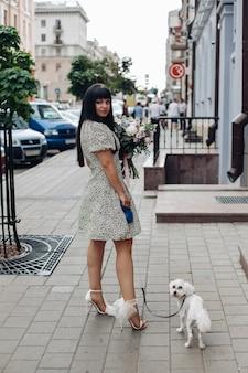 Schönes junges mädchen, das mit kleinem weißen haustierhund auf der stadtstraße im freien haustiere geht...