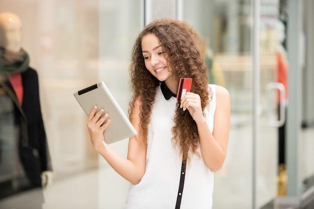 Schönes junges mädchen, das mit kreditkarte für das einkaufen zahlt