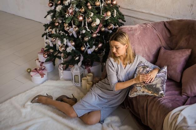 Schönes junges mädchen, das nahe dem sofa auf dem hintergrund des weihnachtsbaums sitzt