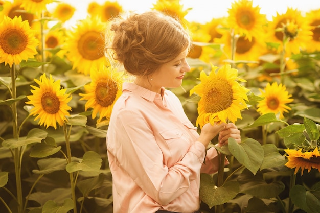 Schönes junges mädchen, das natur auf dem feld von sonnenblumen an einem sonnigen tag genießt