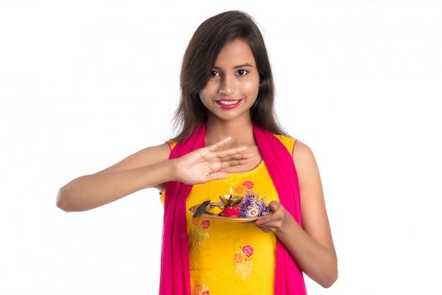Schönes junges mädchen, das pooja thali hält und anbetung durchführt