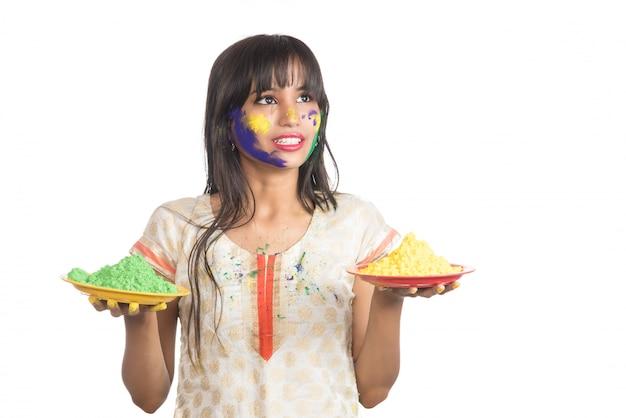 Schönes junges mädchen, das pulverfarbe in platte anlässlich des holi-festivals hält.