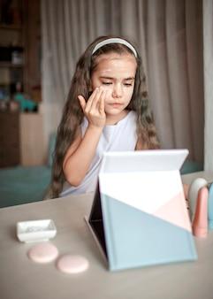 Schönes junges mädchen, das schönheitsmeisterklasse mit tablette online beobachtet und spa-prozedur selbst tut, kind mit glatter maske auf gesicht, schönheitssalon zu hause