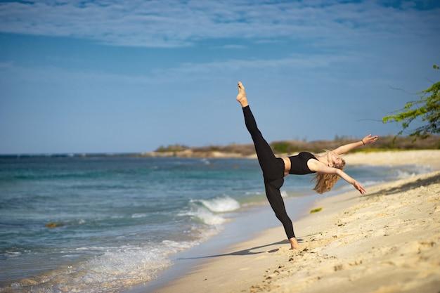 Schönes junges mädchen, das schwarze strumpfhosen trägt, die tanzende posen am strand tun. sommertag und fröhliches urlaubskonzept.
