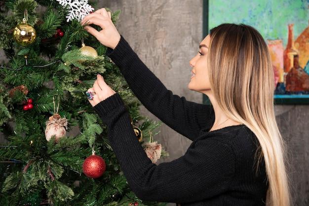 Schönes junges mädchen, das schwarzen pullover trägt, hängt ein spielzeug am weihnachtsbaum. hochwertiges foto