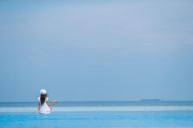 Schönes junges mädchen, das swimmingpool im im freien sich entspannt