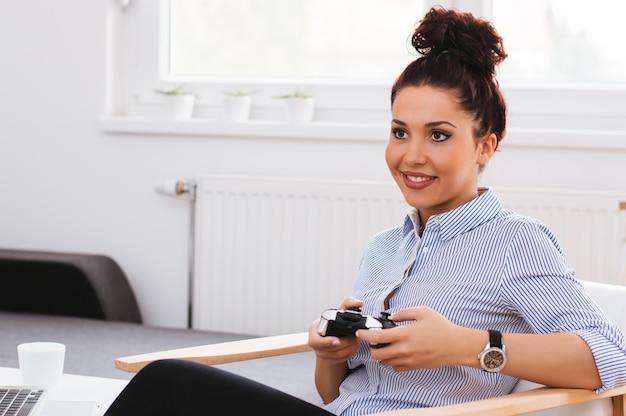 Schönes junges mädchen, das videospiele spielt