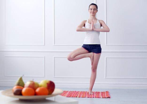 Schönes junges mädchen, das yoga tut