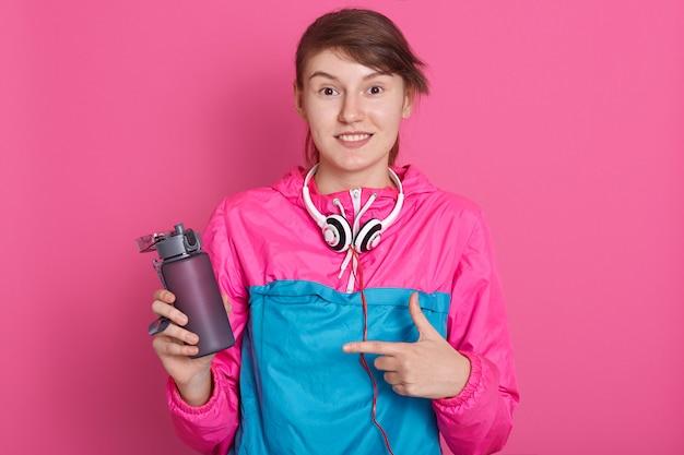 Schönes junges mädchen der schlanken brünette, das sportkleidung aufwirft. sportliches gesundes modell, das auf flasche wasser zeigt