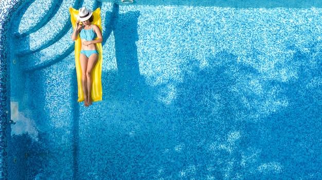 Schönes junges mädchen entspannen im schwimmbad, frau auf aufblasbarer matratze im wasser, luftaufnahme