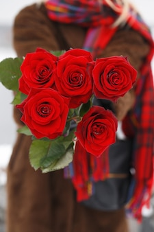 Schönes junges mädchen gibt einen strauß roter rosen am valentinstag