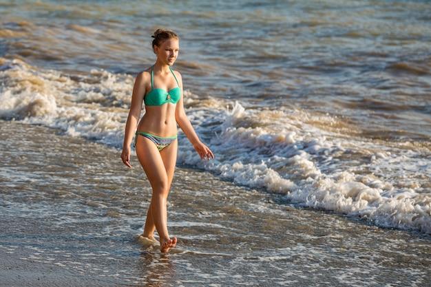 Schönes junges mädchen im badeanzug, der auf dem strand durch das meer an einem sonnigen heißen tag aufwirft.