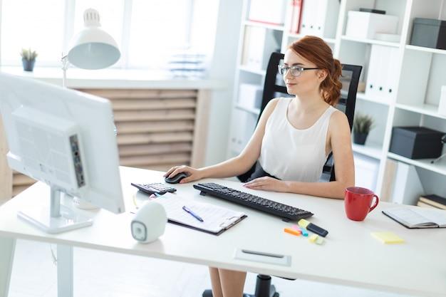 Schönes junges mädchen im büro, das am computer arbeitet.