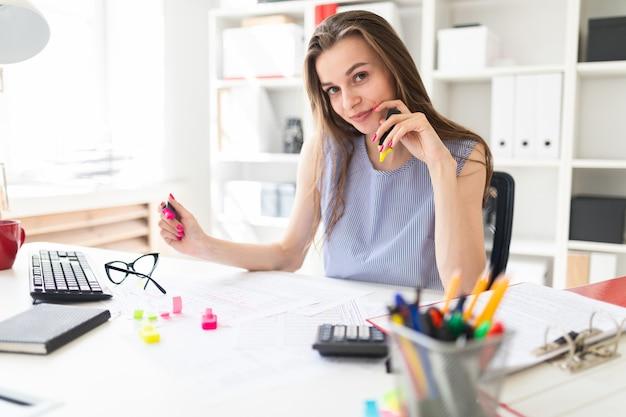 Schönes junges mädchen im büro sitzt an einem tisch und hält in den händen die gelben und rosa markierungen.