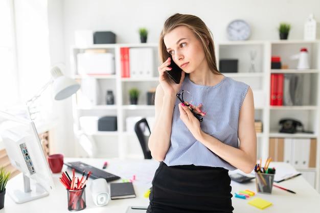 Schönes junges mädchen im büro steht nahe der tabelle, hält gläser in ihrer hand und spricht am telefon.