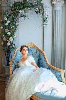 Schönes junges mädchen im reichen kleid, das auf sofa liegt, entspannen sich konzept