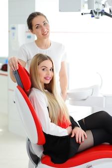 Schönes junges mädchen im roten zahnmedizinischen stuhl
