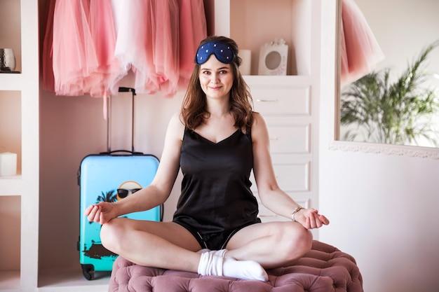 Schönes junges mädchen im schwarzen pyjama am frühen morgen praktiziert yoga in ihrem schlafzimmer. mädchen, das in einem rosa raum sitzt.