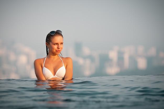 Schönes junges mädchen im weißen bikini, der schwimmt und am rand des pools auf der oberseite des hotels steht