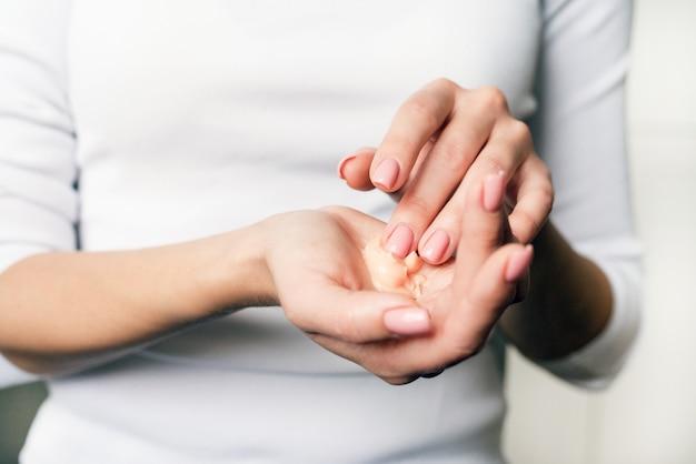 Schönes junges mädchen im weißen langarm befeuchtet ihre hände mit sahne. nägel, die kosmetische handcreme auf weiche seidige gesunde haut auftragen. schönheits- und körperpflegekonzept