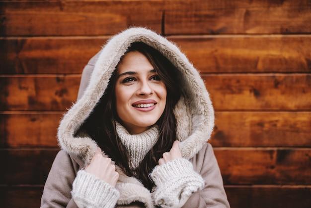 Schönes junges mädchen im wintermantel, der gegen holzwand steht und am schönen wintertag genießt. wegschauen und lächeln.