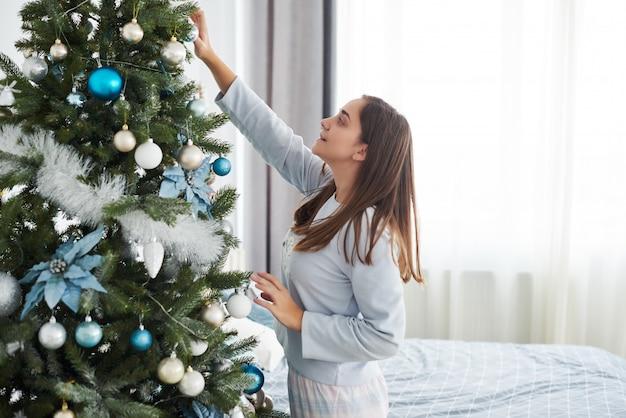 Schönes junges mädchen in den pyjamas den weihnachtsbaum verzierend
