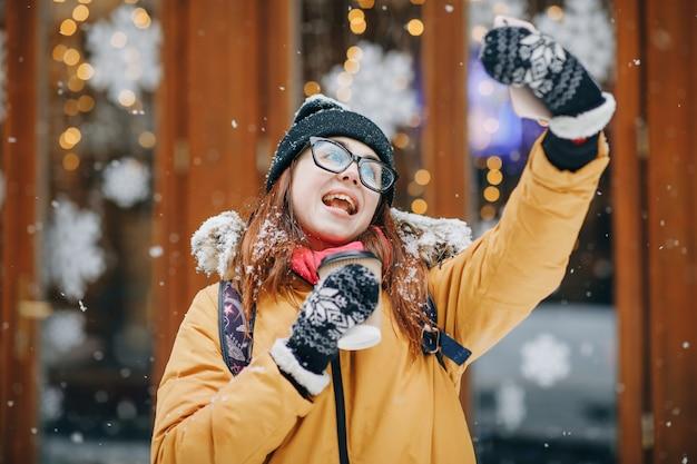 Schönes junges mädchen in der schneebedeckten stadt macht ein selfie. porträt des stilvollen jungen schönen mädchens in einer winterstadt
