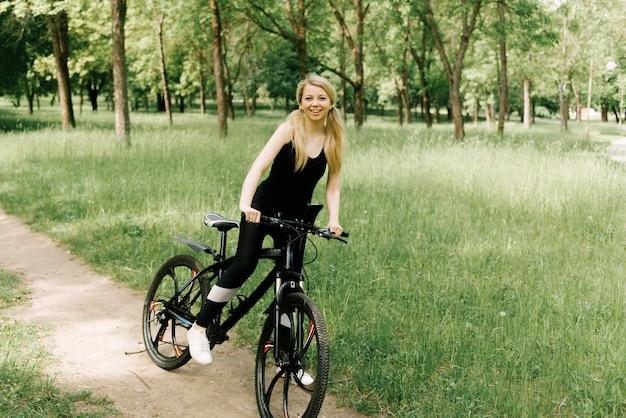 Schönes junges mädchen in der sportuniform, die ein fahrrad im park reitet