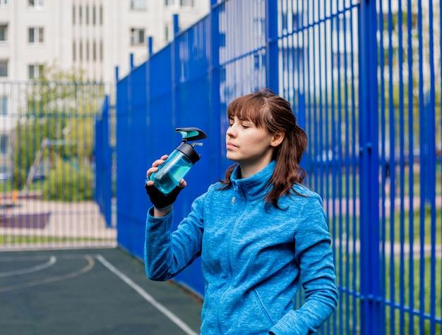 Schönes junges mädchen in der sportuniform trinkwasser von einer flasche auf dem spielplatz. ein brünettes mädchen in einer blauen sportjacke und einer blauen flasche