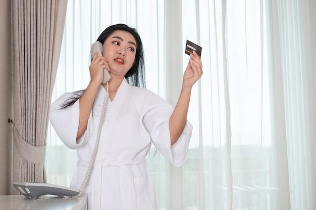 Schönes junges mädchen in einem bademantel im bademantel mit einer kreditkarte