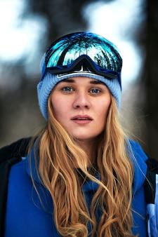Schönes junges mädchen in einem blauen skianzug und -sturzhelm. auf dem kopf befindet sich eine brille zum snowboarden. verschneite berglandschaft. porträt eines reiters. so sieht glück aus.