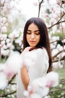 Schönes junges mädchen in einem blühenden garten mit magnolien. magnolienblüte, zärtlichkeit.