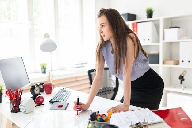 Schönes junges mädchen in einem büro steht nahe einer tabelle und zeichnet eine markierung auf eine magnettafel.