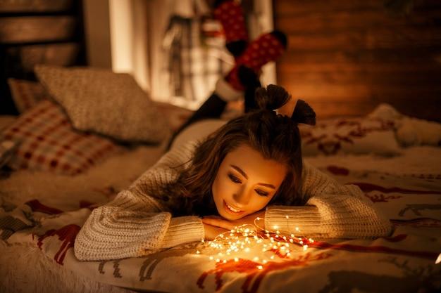 Schönes junges mädchen in einem gestrickten weinlesepullover mit festlichen lichtern auf einem bett an heiligabend