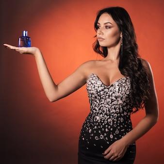 Schönes junges mädchen in einem kleid mit strass zeigt auf der handfläche des parfüms
