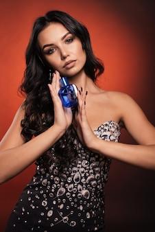 Schönes junges mädchen in einem kleid mit strasssteinen, die parfüm halten