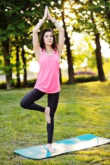 Schönes junges mädchen in einem rosa t-shirt nimmt an eignung oder yoga auf einem hintergrund der natur und des grünen grases teil.