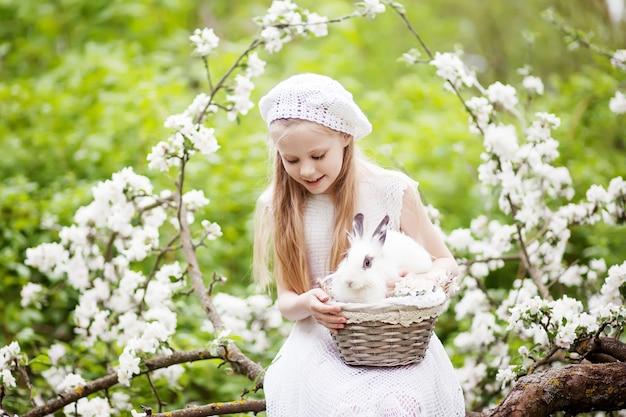 Schönes junges mädchen in einem weißen kleid, das mit weißem kaninchen im frühlingsblütengarten spielt. frühlingsspaß für kinder. osterzeit
