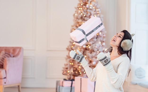 Schönes junges mädchen in einem weißen kleid wirft ein geschenk.